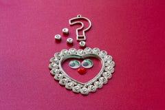Coração com olhos do brinquedo, ponto de interrogação e o amor da inscrição foto de stock royalty free