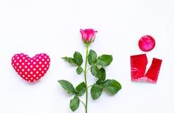 Coração com rosa e o preservativo vermelho no fundo branco foto de stock royalty free