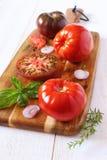 Coração com tendência para a alta dos tomates na placa de corte Imagens de Stock