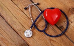 Coração com um estetoscópio médico, isolado no fundo de madeira Fotos de Stock