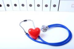 Coração com um estetoscópio médico, isolado no fundo de madeira foto de stock