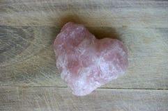 Coração cor-de-rosa de pedra preciosa no fundo de madeira Foto de Stock Royalty Free
