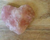 Coração cor-de-rosa de pedra preciosa no fundo de madeira Fotografia de Stock Royalty Free