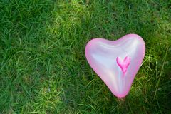 Coração cor-de-rosa o balão dado forma no fundo da grama para o amor e valen fotografia de stock royalty free