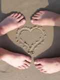Coração da areia com pé dos amantes Fotografia de Stock