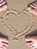 Coração da areia com pé dos amantes Imagem de Stock Royalty Free
