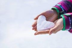 Coração da bola de neve da terra arrendada da menina nas mãos Imagem de Stock Royalty Free