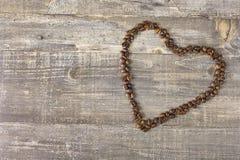Coração da tabela textured bonita do fundo de madeira dos feijões de café Fotos de Stock Royalty Free
