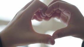 Coração dado forma pelas mãos da criança As crianças bonitos descrevem a forma do coração com seus dedos perto acima Conce video estoque