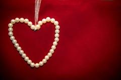 Coração das pérolas brancas no fundo vermelho Imagens de Stock