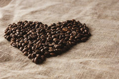 Coração de feijões de café em horizontal de linho Imagens de Stock Royalty Free