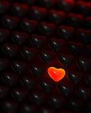 Coração de incandescência do vermelho-vidro cercado de cor escuros Imagens de Stock Royalty Free