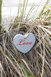 Coração de madeira azul inscrito em dunas da praia imagens de stock