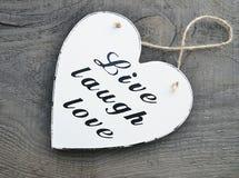 Coração de madeira branco decorativo com o amor vivo do riso do slogan no fundo de madeira cinzento Vivo, riso, amor Imagem de Stock Royalty Free