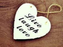 Coração de madeira branco decorativo com o amor vivo do riso do slogan no fundo de madeira velho Vivo, riso, amor Imagens de Stock