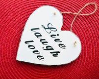 Coração de madeira branco decorativo com o amor vivo do riso do slogan no fundo vermelho do guardanapo da palha Vivo, riso, amor Fotografia de Stock