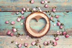 Coração de madeira com as flores cor-de-rosa secadas no de madeira velho de turquesa Imagem de Stock Royalty Free