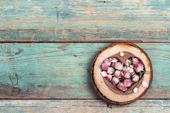 Coração de madeira com as flores cor-de-rosa secadas no de madeira velho de turquesa Imagem de Stock