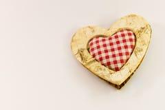 Coração de madeira com a matéria têxtil esquadrada no meio Imagem de Stock