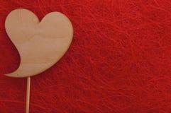 Coração de madeira em um fundo vermelho Fotos de Stock