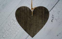 Coração de madeira escuro grande no fundo de madeira branco Feche acima e copyspace grande para seu texto imagens de stock royalty free