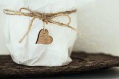 Coração de madeira no saco branco com corda Imagens de Stock