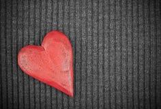 Coração de madeira vermelho no fundo feito malha Fotografia de Stock