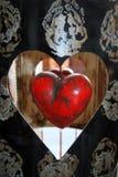 Coração de madeira vermelho no preto e no quadro do metal do ouro imagens de stock