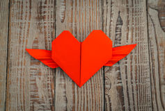 Coração de papel vermelho do origâmi com as asas no fundo de madeira Imagens de Stock