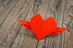 Coração de papel vermelho do origâmi com as asas no fundo de madeira Fotos de Stock