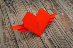 Coração de papel vermelho do origâmi com as asas no fundo de madeira Foto de Stock