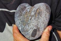 Coração de pedra em suas mãos imagens de stock