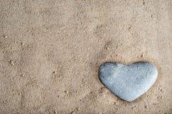 Coração de pedra na areia fotografia de stock