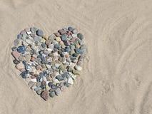 Coração de pedra na areia na praia imagens de stock royalty free