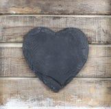 Coração de pedra no fundo de madeira Fotos de Stock