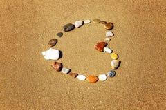 Coração de pedras na costa arenosa foto de stock
