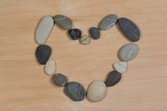 Coração de pedras na madeira Fotos de Stock