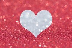 Coração de prata do brilho no fundo vermelho imagem de stock
