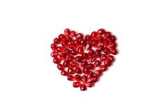 Coração de sementes da romã em um fundo branco Imagens de Stock