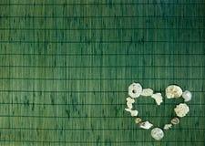 Coração de Shell no fundo de bambu verde Fotografia de Stock Royalty Free