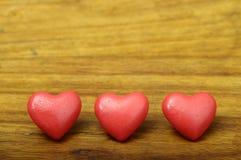 Coração de três vermelhos no fundo de madeira Imagens de Stock