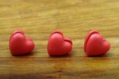 Coração de três vermelhos no fundo de madeira Imagem de Stock Royalty Free