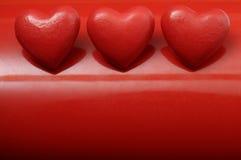 Coração de três vermelhos no fundo vermelho Imagem de Stock