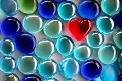 Coração de vidro vermelho com os grânulos de vidro azuis do foco macio Foto de Stock Royalty Free
