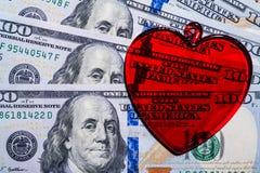 Coração de vidro vermelho em notas de dólar Fotos de Stock