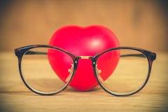 Coração de vidros vestindo do amor em de madeira Imagem de Stock Royalty Free
