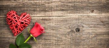 Coração de vime vermelho e flor cor-de-rosa no fundo de madeira Fotografia de Stock