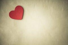 Coração decorativo de madeira vermelho no fundo de pano. Tom do Sepia imagens de stock royalty free