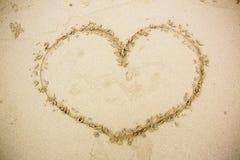 Coração desenhado na areia Seashell do Scallop na cor-de-rosa imagens de stock royalty free