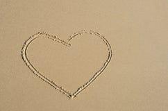 Coração desenhado na areia Seashell do Scallop na cor-de-rosa fotografia de stock royalty free